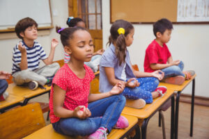Mixed race pupils meditating in lotus position on desk in classr